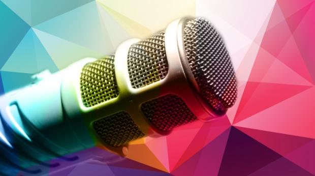 Descrição da imagem: um microfone e tem aplicado um efeito aplicado na imagem de vários triângulos coloridos da esquerda para a direita vai do azul ao rosa, com tons de roxo e laranja ao meio.